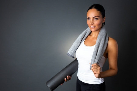 Smiling fitness woman posing with yoga mat, isolated on dark grey background.