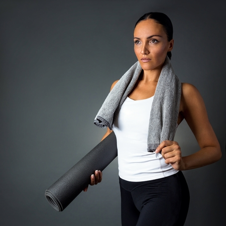 Beautiful fitness woman posing with yoga mat, isolated on dark grey background.