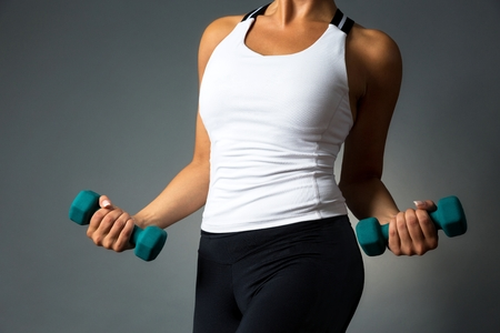 hands on waist: Waist and hands of a beautiful sporty muscular woman working out with two dumbbells, isolated against dark grey background. Stock Photo