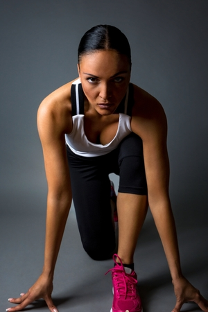 simulating: Young fitness woman,simulating race start position.Isolated against dark background. Stock Photo