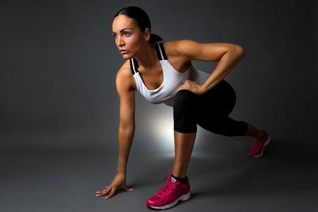 de rodillas: Mujer atractiva de la aptitud de preformado ejercicios de estiramiento. Aislado contra el fondo oscuro.