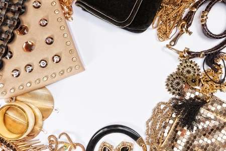 Woman shiny accessories grouped around empty space for text. Top view.