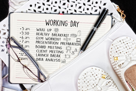 light duty: Modern businesswoman working day schedule.White purse and shoes next to open note book. Top view. Stock Photo