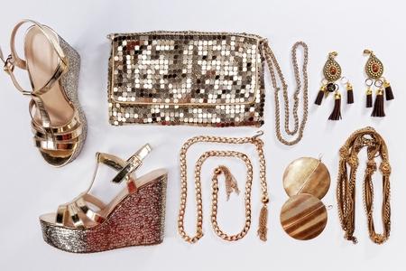 スタイリッシュな女性服。黄金色の宝石、光沢のあるゴールドの財布、サンダル、白い背景で隔離。 写真素材