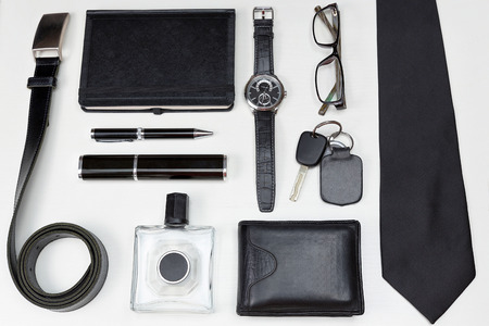 car accessory: Men accessories. Black elegant accessories pieces isolated on white wooden table. Top view.