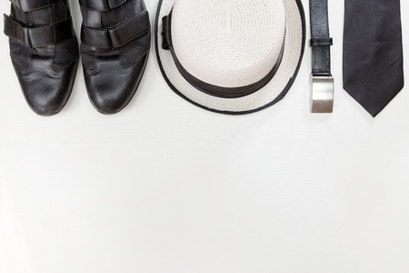 cuff links: Stylish man accessories. Black leather shoes, belt , isolated on white wooden table. Top view.