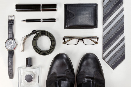 남성 액세서리. 검은 우아한 액세서리 조각 흰색 나무 테이블에 격리. 평면도. 스톡 콘텐츠