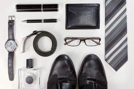 Akcesoria dla mężczyzn. Czarne eleganckie akcesoria sztuk na białym drewnianym stole. Widok z góry.