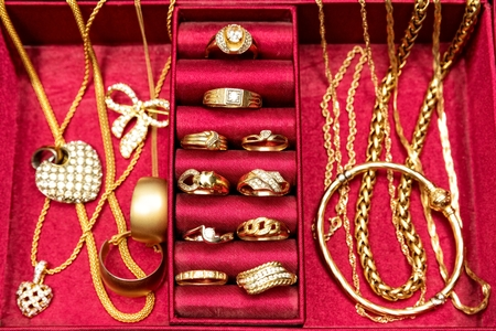 jewelry chain: Golden rings,necklace,bracelet and other gold pieces of jewelry,set inside red jewelry box. Top view.