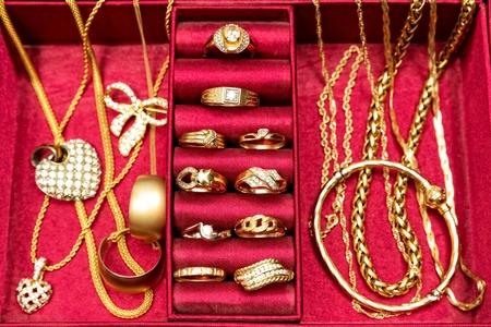 Gouden ringen, ketting, armband en andere gouden sieraden, ingesteld binnen rode sieraden doos. Bovenaanzicht.