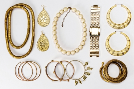 Woman accessories,gold and yellow,against white background.Top view. Standard-Bild