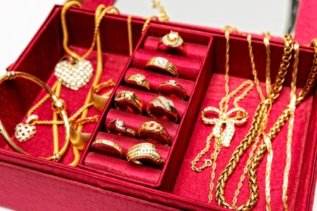 Golden rings,necklace,bracelet and other gold pieces of jewelry,set inside red jewelry box. Zdjęcie Seryjne