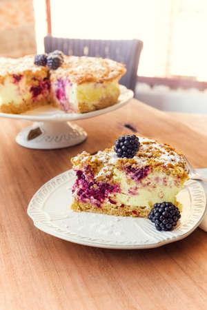 trozo de pastel: Pedazo de pastel al horno con crema de fruta, establecer en mesa de madera en la cafetería.