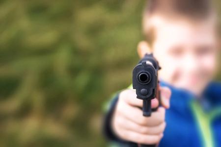 pistola: El muchacho joven, con una pistola de juguete, sobre fondo verde hierba.