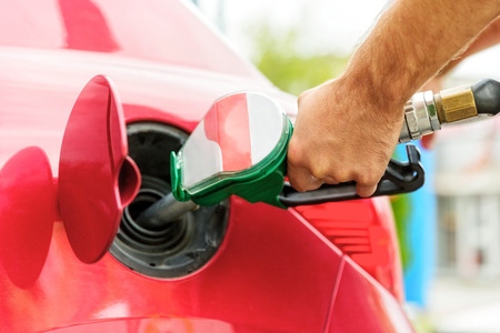 high price of oil: Close up of a worker hand, loading gas into car. Gas station.