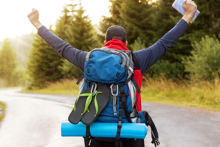 yoga mat: Joyful male back packer is arriving to the end point of his journey.