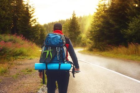packer: Male back packer walking down the mountain road,against sunset.