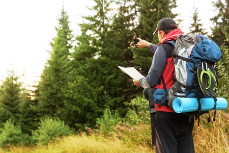 packer: Male back packer, adventurist, looking for mountain route,with a map in his hand.