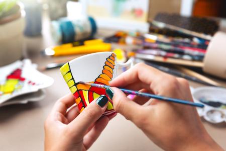 ceramica: Cerca de la pintura en manos femeninas en la taza de cerámica.