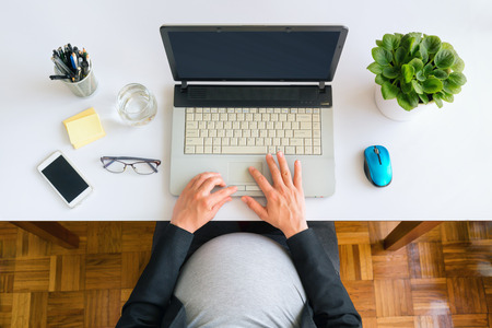 Pregnant business woman sitting at the desk and working on the laptop. Top view.