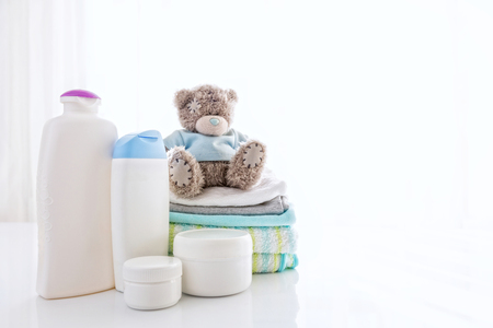 item: Several cosmetics product for children next to towels and teddy bear.