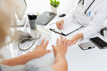 artrosis: Primer plano de una mujer de mediana examination.Middle médica con la artritis que muestra sus manos a una mujer médico.