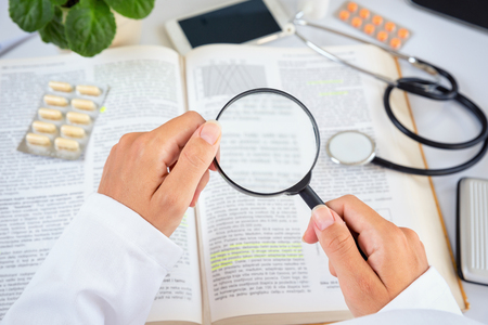 studding: Close up of a female doctor reading professional literature with magnifying glass.