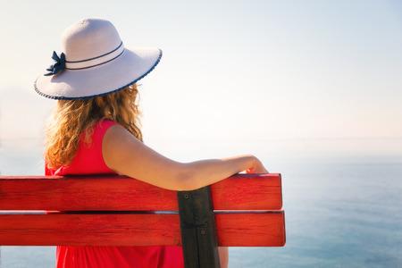 horizonte: Mujer joven en vestido rojo, el emplazamiento en el banco y mirando al horizonte.