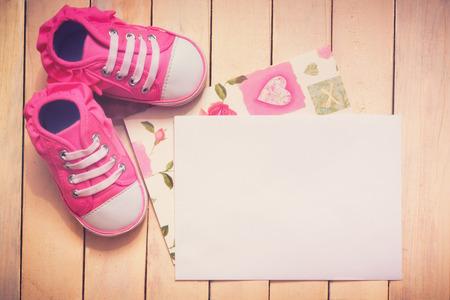 Es una niña, tarjeta. Zapatos de color rosa al lado de la tarjeta blanca vacía. Foto de archivo - 70639311