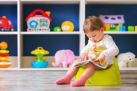 Cute little baby girl,sitting on potty and reading.