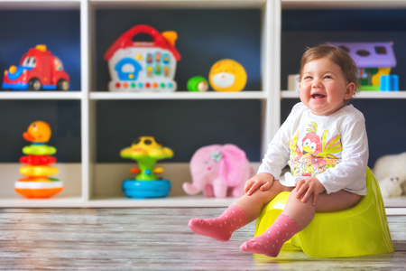 Smiling baby girl, sitting on chamber pot . Stock Photo