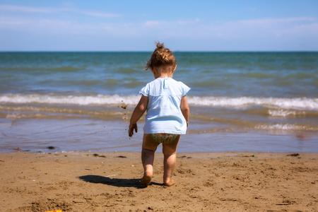 Toddler girl walking on the beach.