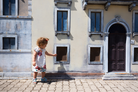 Toddler girl playing in front of the building facade. 版權商用圖片
