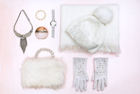 Woman winter fashion outfit. Top view of white winter accessories, isolated on light pink background.