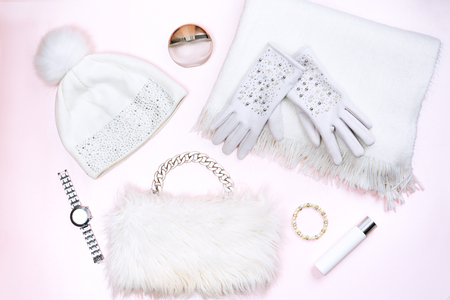 Lady`s winter fashion outfit. Top view of white winter accessories set, isolated on light pink background.