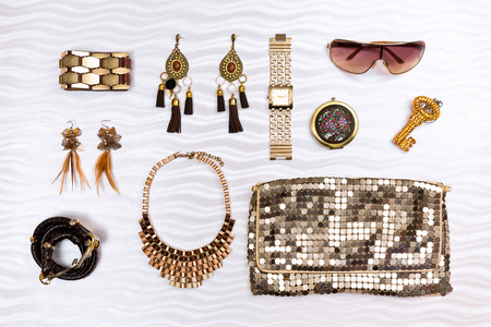 Gold modern woman fashion accessories, isolated on white textured background.