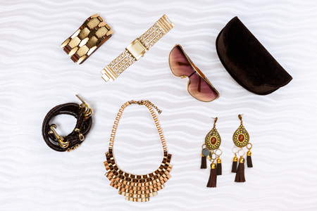 Gold and brown modern woman fashion accessories, isolated on white textured background.