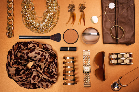 Trendy woman accessories. Brown, beige and ocher modern outfit. Jewelry, make up, and clothes. Top view.