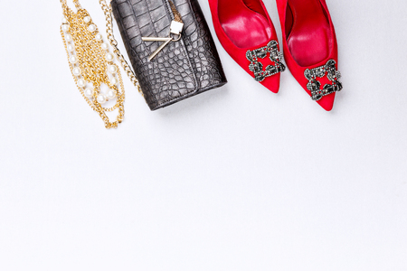 Trendy woman accessories. Attractive high hill red shoes, next to leather purse and gold necklace. Top view.