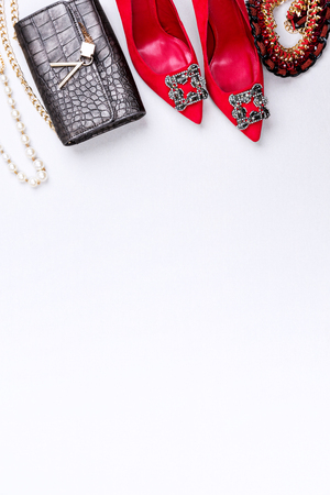 Trendy woman accessories. Attractive high hill red shoes, next to leather purse and necklace. Top view. Vertical composition. Banco de Imagens