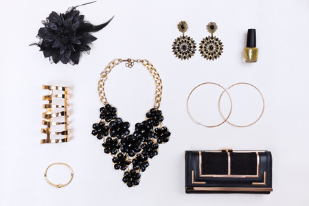 Trendy woman accessories. Black and gold modern jewelry. Top view.