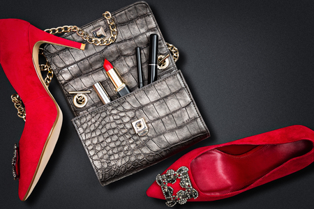 Luxury woman accessories. Handbag and high heels, isolated on dark background. Top view.