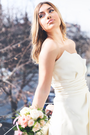 Young beautiful bride wearing modern wedding dress, posing on the balcony, on day light. Banco de Imagens