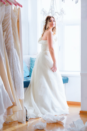 Lovely and romantic wedding moments. Beautiful model, wearing long white dress and posing next to window, inside salon.