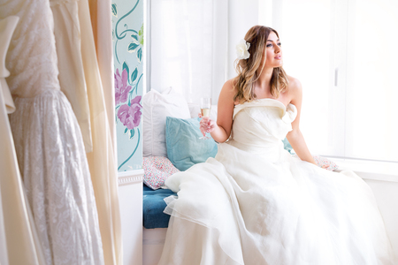 Lovely and romantic wedding moments. Beautiful model wearing wedding dress, and sitting on blue sofa, next to window, inside salon.