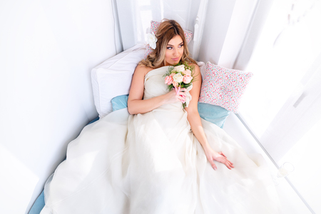 Romantic wedding moments. Beautiful young bride sitting on blue sofa and holding flower bouquet. Banco de Imagens