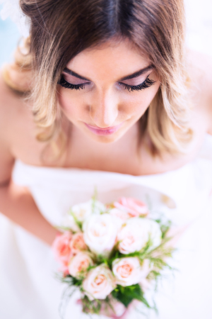 Romantic wedding moments. Portrait of a beautiful young bride holding flower bouquet. Top view.