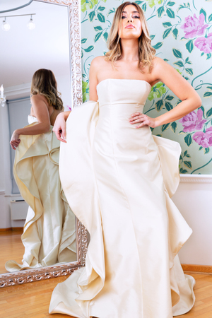 Attractive young model in wedding dress, posing next to mirror, inside salon.