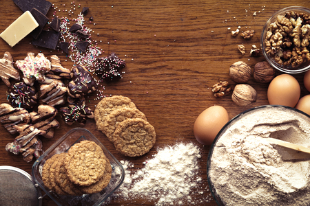 Homemade delicious cookies and ingredients on top of the kitchen wooden table. Banco de Imagens