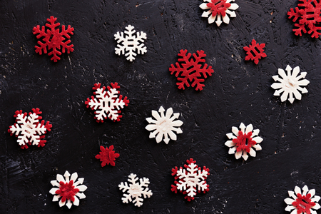 Beautiful wooden red and white Christmas decoration snowflakes against dark background. Top view.